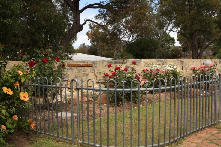 Memorial rose garden with a fence around it.